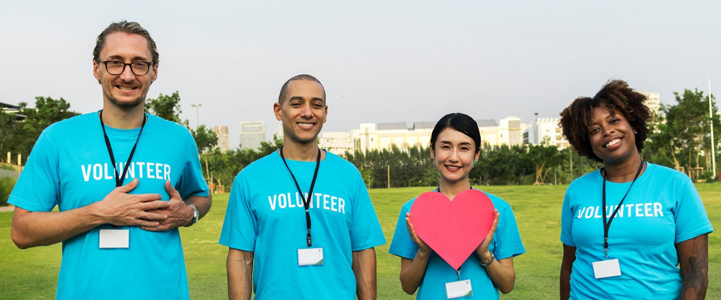 four people in volunteer t shirts with one holding a paper heart