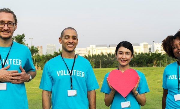 a diverse group of volunteers hold cutout hearts