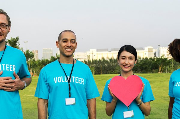 a group of volunteers stand together holding paper hearts