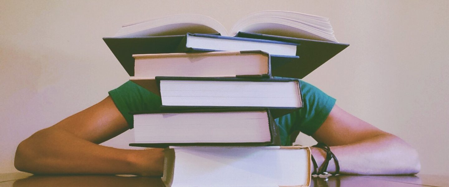 person leaning on desk with their head blocked by a stack of books
