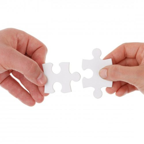 two hands connect pieces of a puzzle together