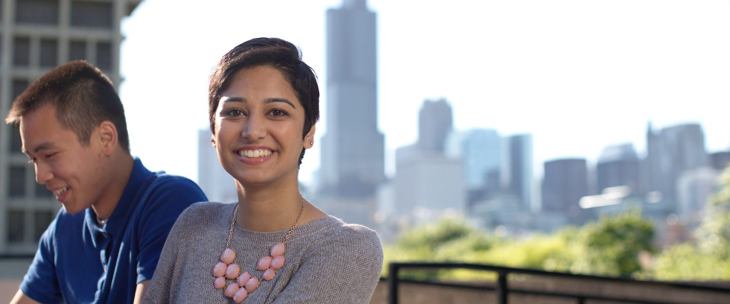 A young adult female smiles at the camera with the Chicago skyline in the background