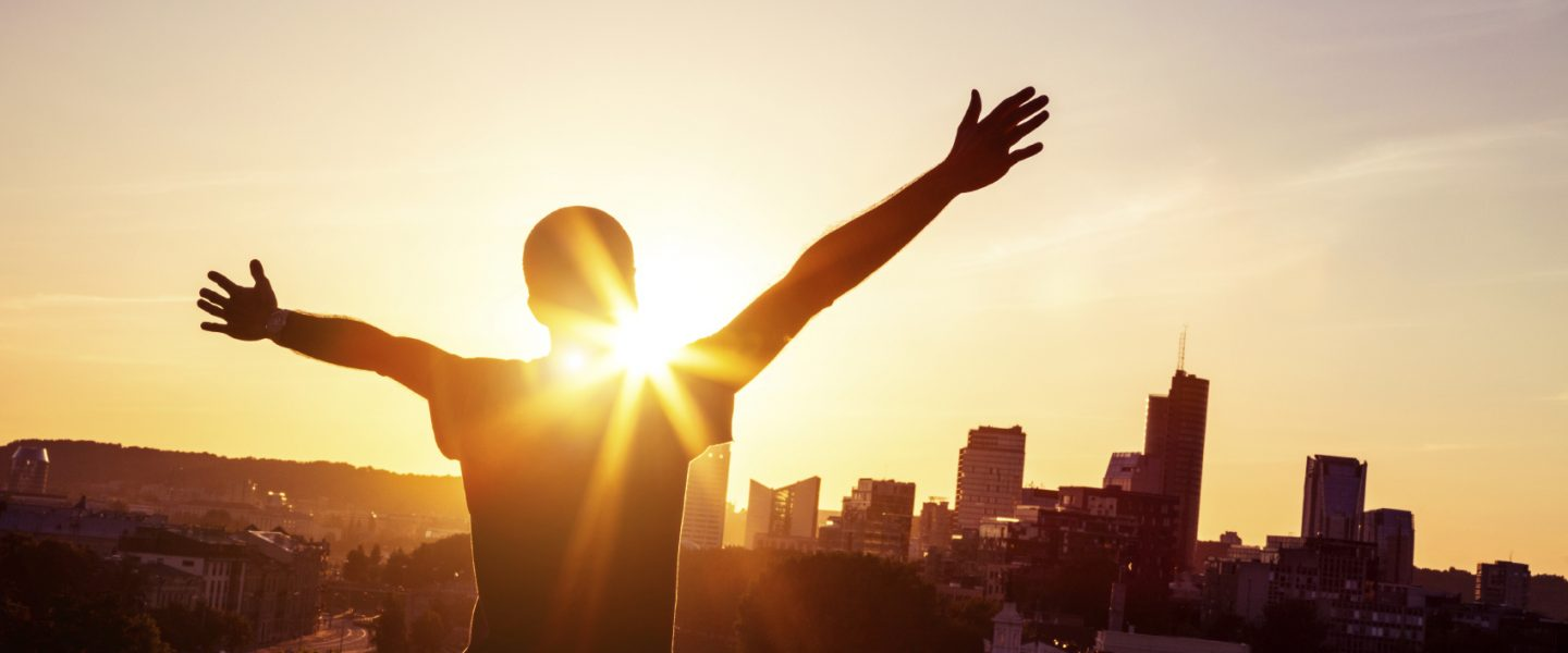 a person standing with their arm spreads while the sun rises over a city skyline in the background