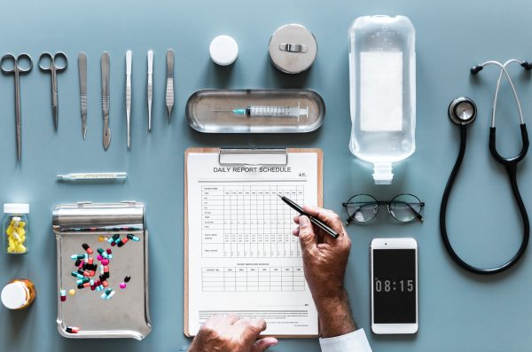 clinical research tools and devices, including scissors, pill bottles, clipboard, syringe, IV bag, glasses, phone and stethoscope