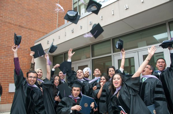 a group of dentistry graduates throw their hats in the air