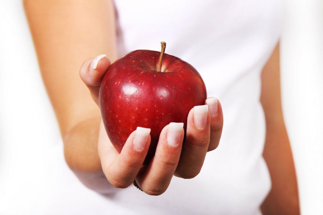 a woman's hand offers a red apple