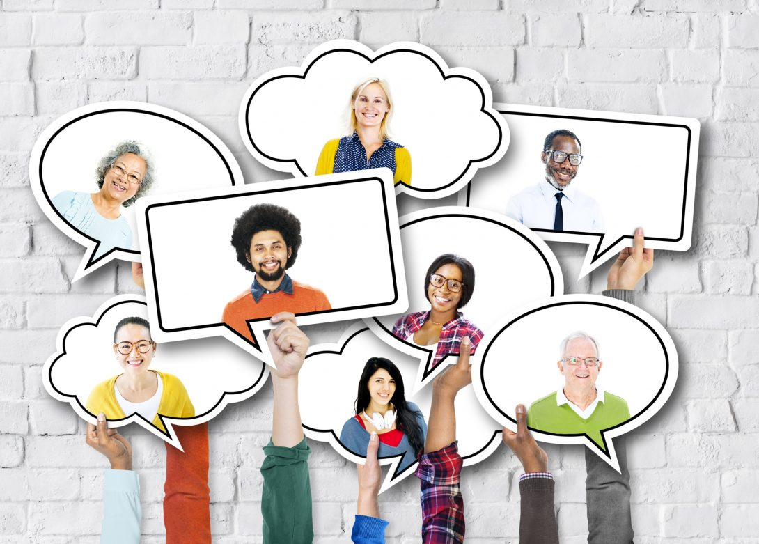 hands hold up cutout speech bubbles containing the faces of a diverse group of men and women