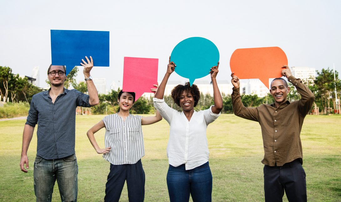 a diverse group of men and women hold up speech bubble cut outs