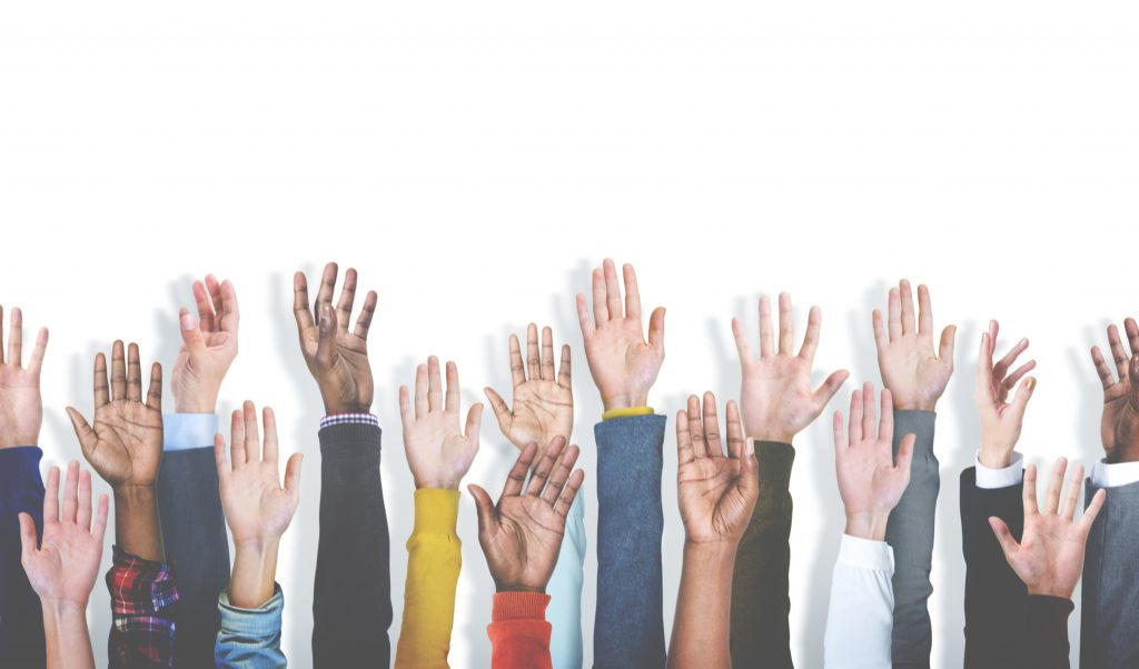 a diverse array of hands raised in the air
