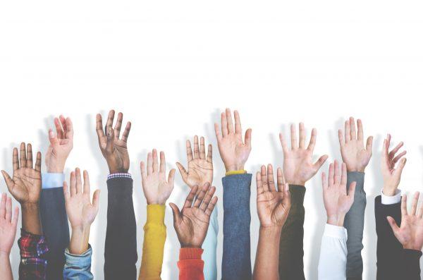 multiple diverse hands raised as if volunteering