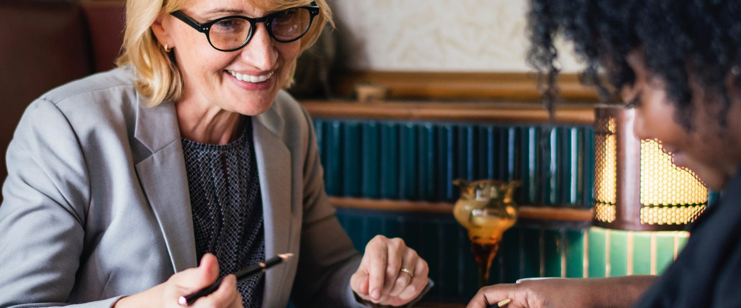 blonde woman in a suit is seated at a table providing guidance to a younger woman over coffee