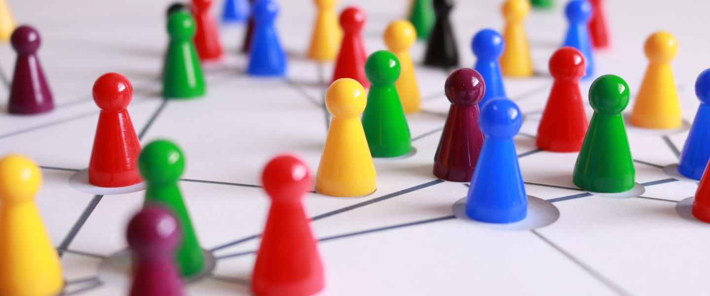 multicolored pawns are placed on a board with network lines connecting them