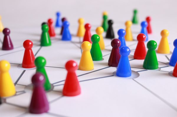 colorful pawns are placed on a board with networking connections between them