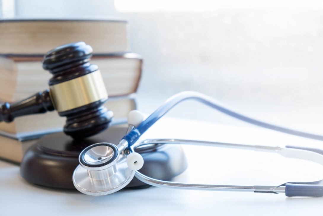 books and a judge's gavel behind a stethoscope
