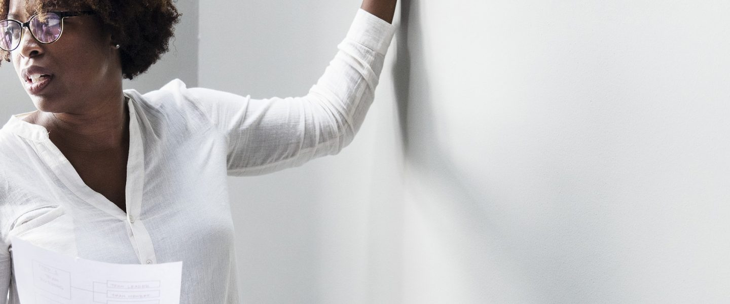 an african american woman holds a paper in one hand and a marker in the other preparing to write on the wall