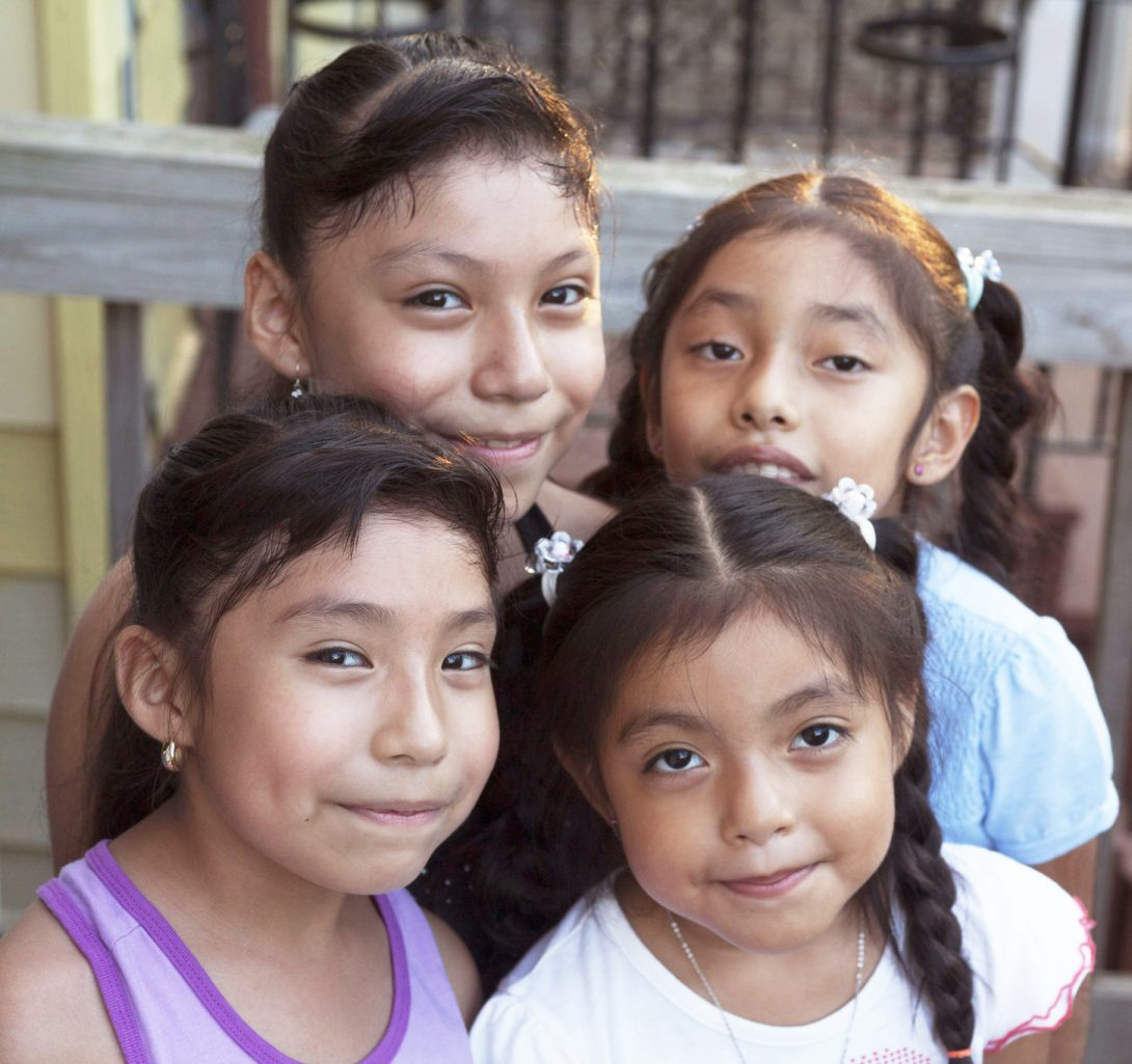a group of young hispanic girls smile at the camera