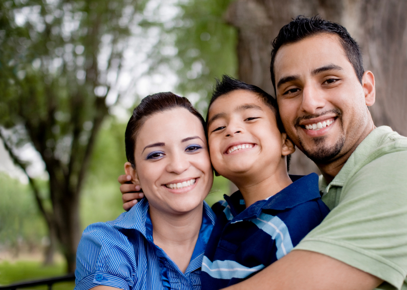 a man and woman hug their son while smiling at the camera
