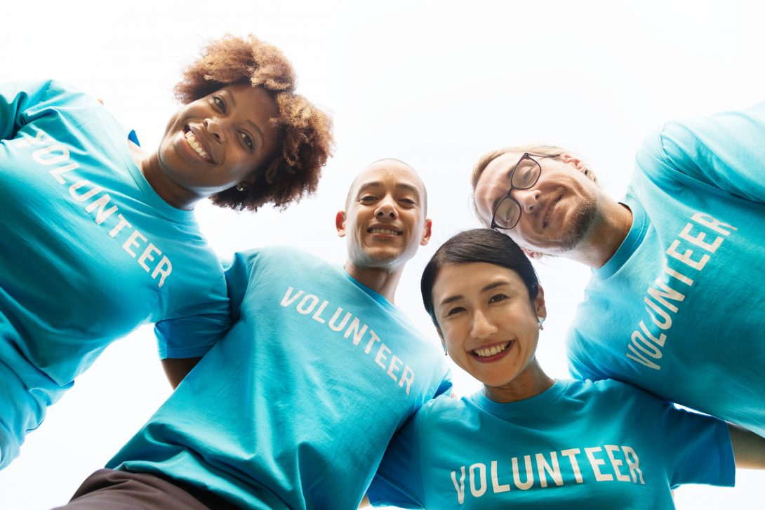 a diverse group of volunteers smile down at the camera