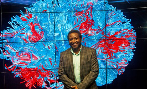 Dr. Ajilore standing in front of an abstract map of the brain