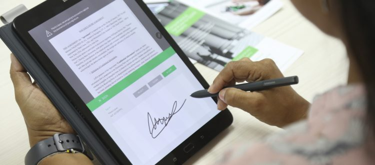 a woman signs her e signature on an electronic tablet