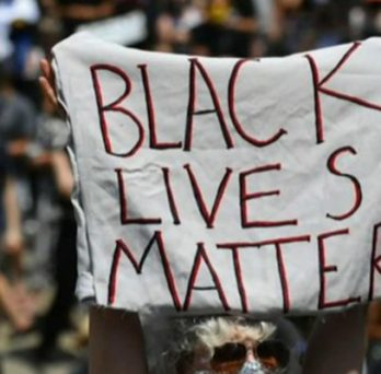 a protestor holds a sign that reads Black Lives Matter
