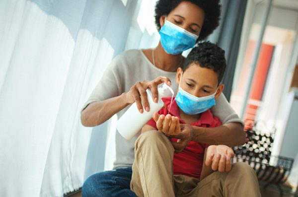 a mother wearing a surgical mask helps her son, also wearing a mask, apply hand sanitizer
