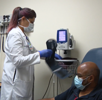 a clinical research nurse takes the vitals of a masked african american study volunteer