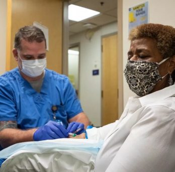 """Registered nurse Corey Ringhisen prepares to draw blood from Bonita """"Bonnie"""" Blue at UI Health during a vaccine clinical trial led by Dr. Richard Novak at UIC last summer. (Joshua Clark/University of Illinois Chicago)"""