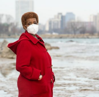 Bonnie Blue stands near Lake Michigan in a red coat and face mask