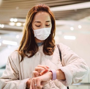 a young woman wearing a face mask checks her smart watch
