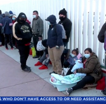 a line of masked immigrants wait outside a facility