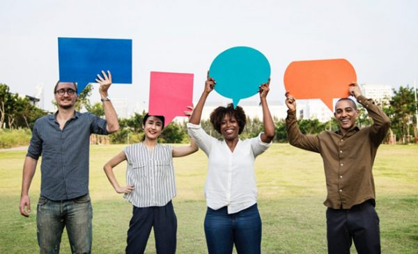 a diverse group of men and women hold up speech bubble cutouts