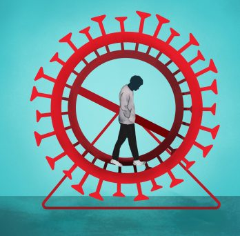 a person stands head down on a hamster wheel that looks like a covid19 virus