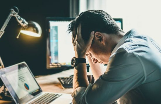 a man holds his head in frustration while looking at his laptop