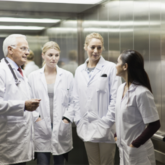 a group of health care workers talking in an elevator