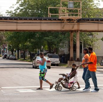 a family crosses a street in the Englewood Chicago neighborhood