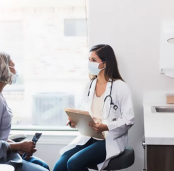 a masked woman consults with a masked physician in a clinic room