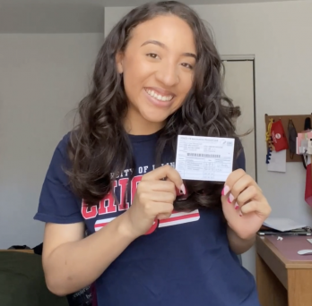 UIC student Terrice Randolph poses with her vaccine card in social media video