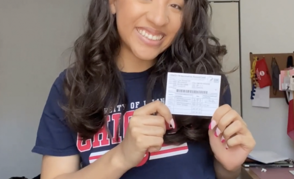 UIC student smiling holding a vaccination card