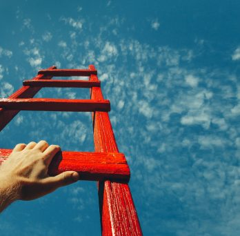 a hand grips a red ladder ascending into a blue sky