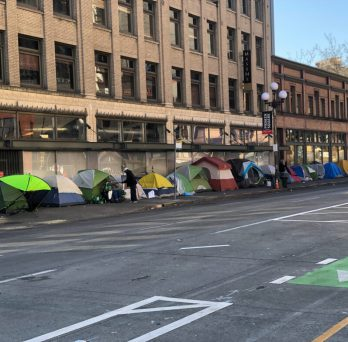 Tents for homeless people line a city sidewalk. Photo: 400tmax, Getty Images